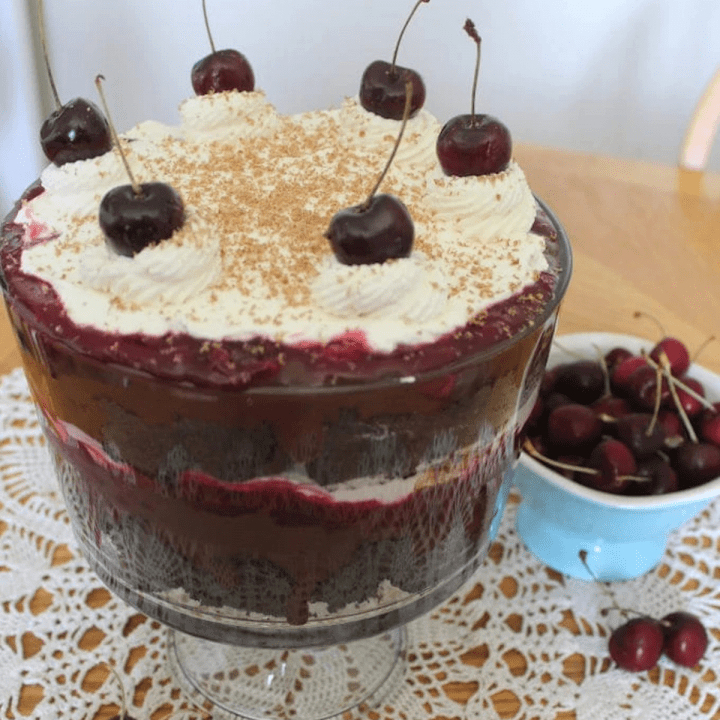 A trifle with a bowl of cherries beside it.