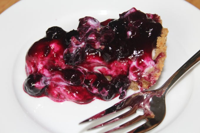 Blueberry cheesecake pie on a white plate with a fork