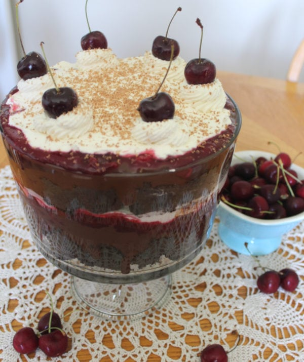Black forest trifle in a trifle bowl with whole cherries scattered around it.