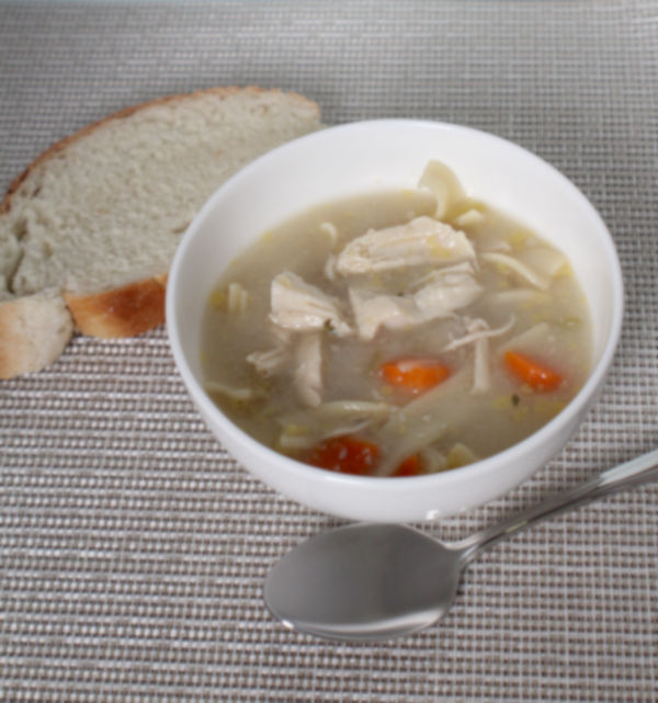 chicken noodle soup in a bowl alongside a spoon and a piece of bread.
