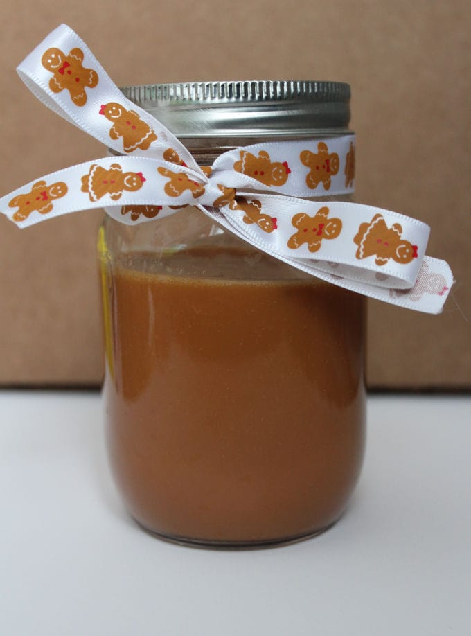 Cajeta in a mason jar decorated with ribbon.