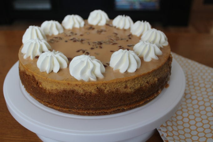 A pumpkin cheesecake on a cake stand.