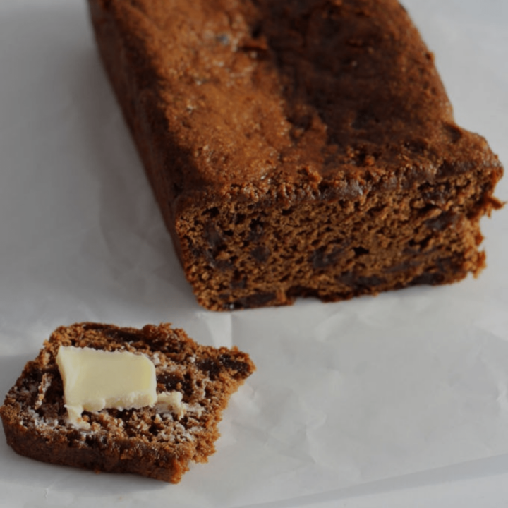 Malt bread loaf with a slice cut from it. The slice has butter on it.