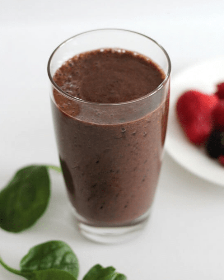 A smoothie in a clear glass with spinach leaves and berries around it.