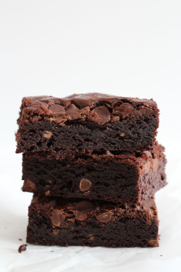Three fudge brownies stacked on a piece of parchment paper.