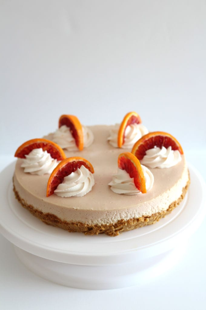 Blood Orange Cheesecake decorated with whipped cream and slices of blood oranges.