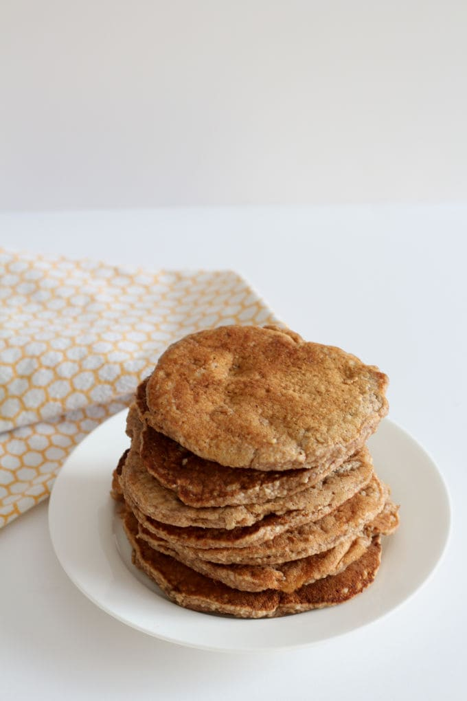 Spiced pancakes for babies and toddlers on a white plate with an orange and white tea towel in the background