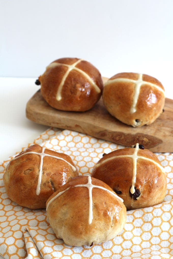 Hot cross buns on an orange and white tea towel.
