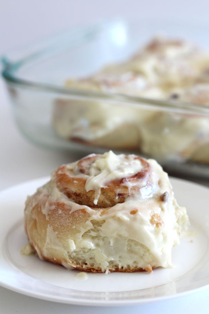 Cinnamon roll with cream cheese frosting on a plate.