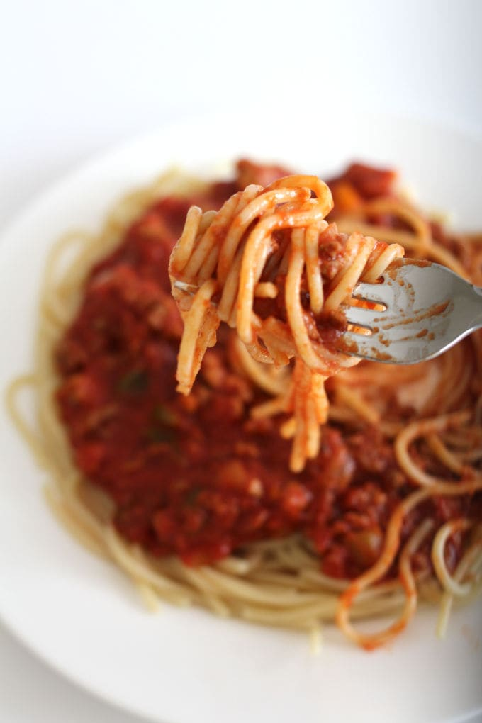 A forkful of spaghetti and meat sauce with a plate of it in the background.