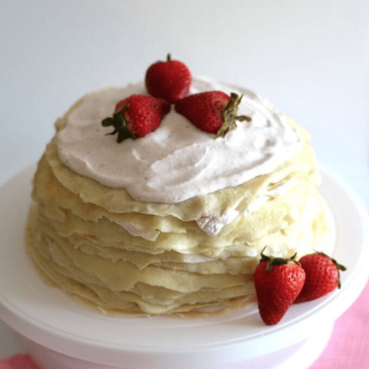 A crepe cake on a cake plate with strawberries at it's base.