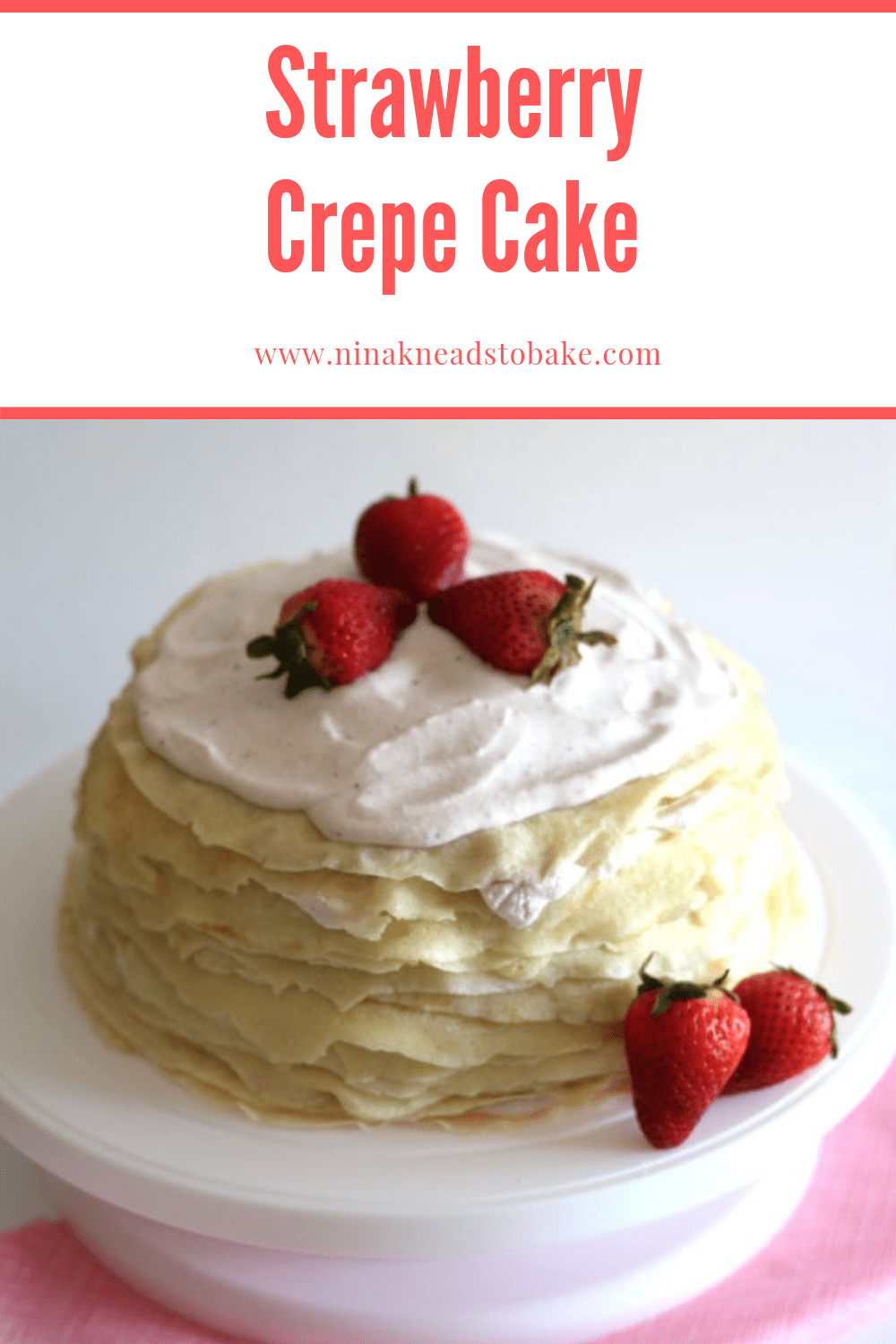 A strawberry crepe cake on a cake stand.