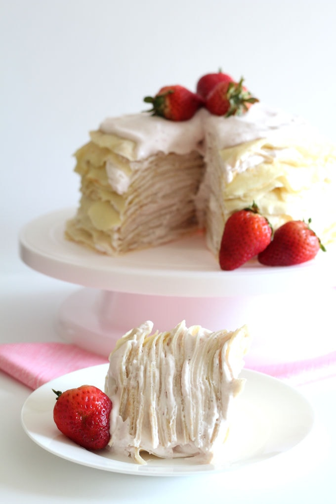 A slice of crepe cake on a plate with the rest of the strawberry crepe cake in the background.