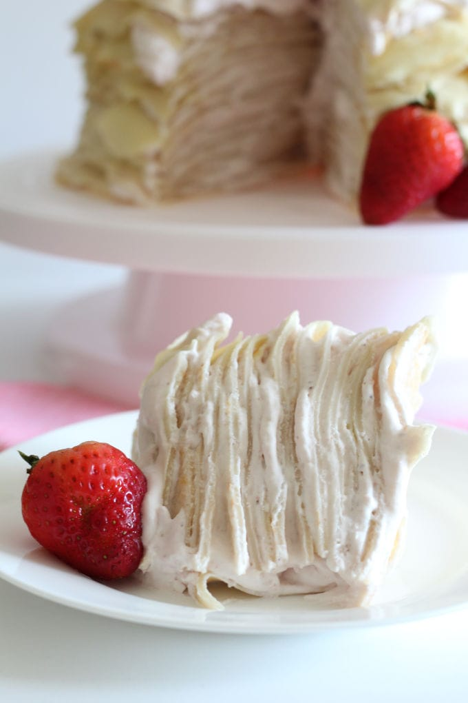 A close up of a slice of crepe cake on a plate with the rest of the strawberry crepe cake in the background.