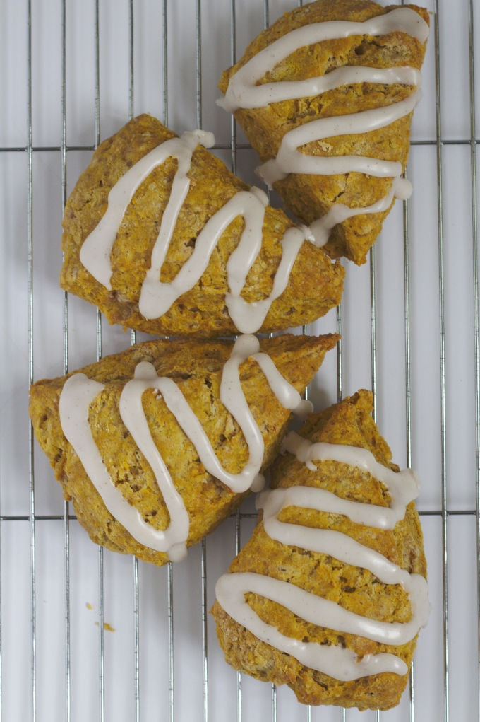 Four pumpkin spice scones arranged in a half circle pattern.