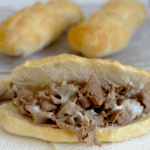 A philly cheesesteak with extra buns behind it.
