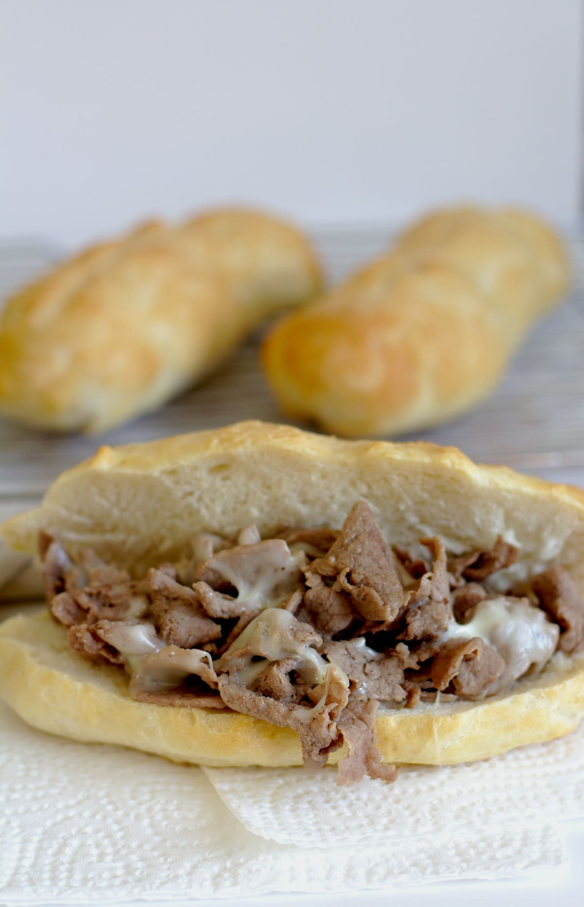 A philly cheesesteak in front of more buns.