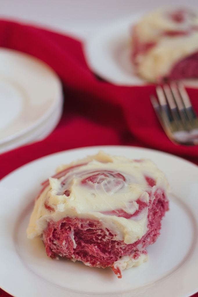 A red velvet cinnamon roll an a plate.