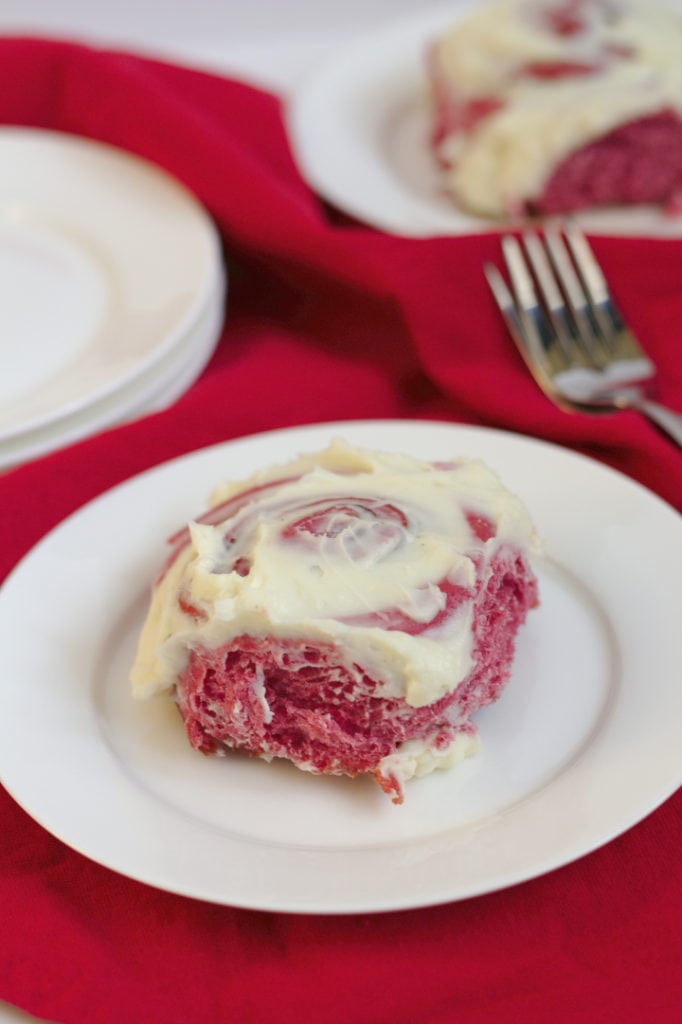 A red velvet cinnamon roll on a plate.