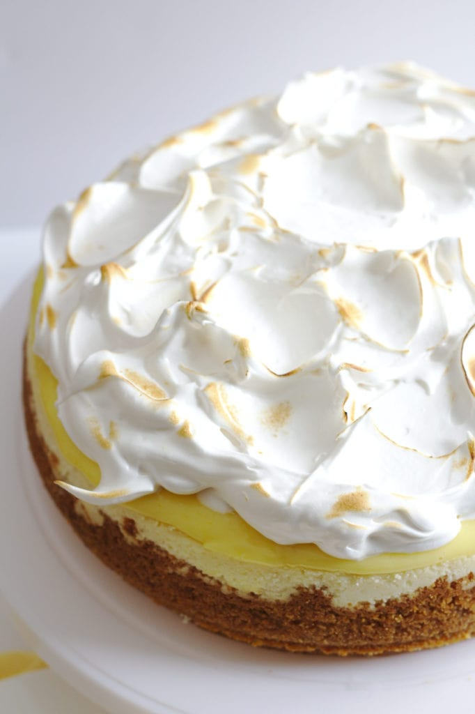 A partial view of a cheesecake on a plate stand.