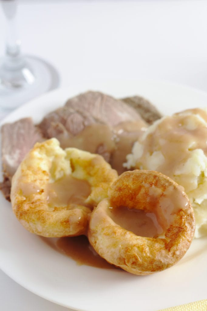 A plate of roast beef, mashed potatoes and Yorkshire pudding with a glass of red wine in the background.