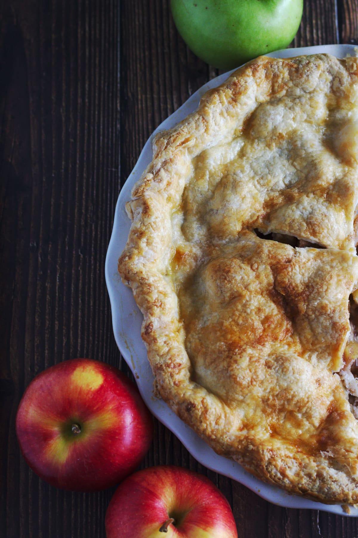 A pie with apples around it.