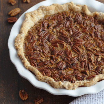 A whole pecan pie in a pie dish.