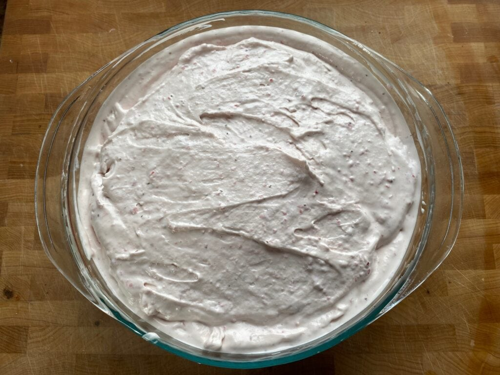 The ice cream has been churned and is placed into a container to go into the freezer.