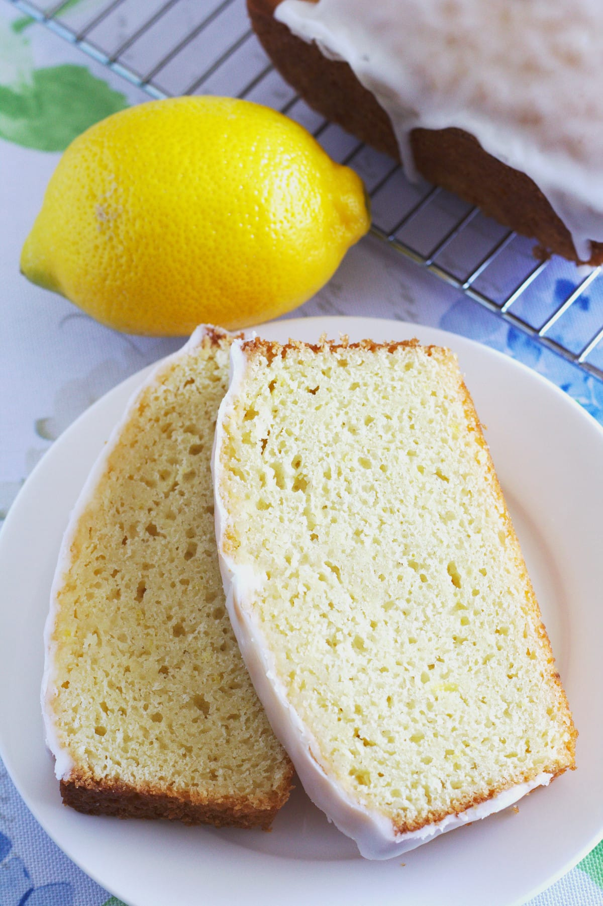 Two slices of lemon loaf on a plate with a lemon and the rest of the loaf.