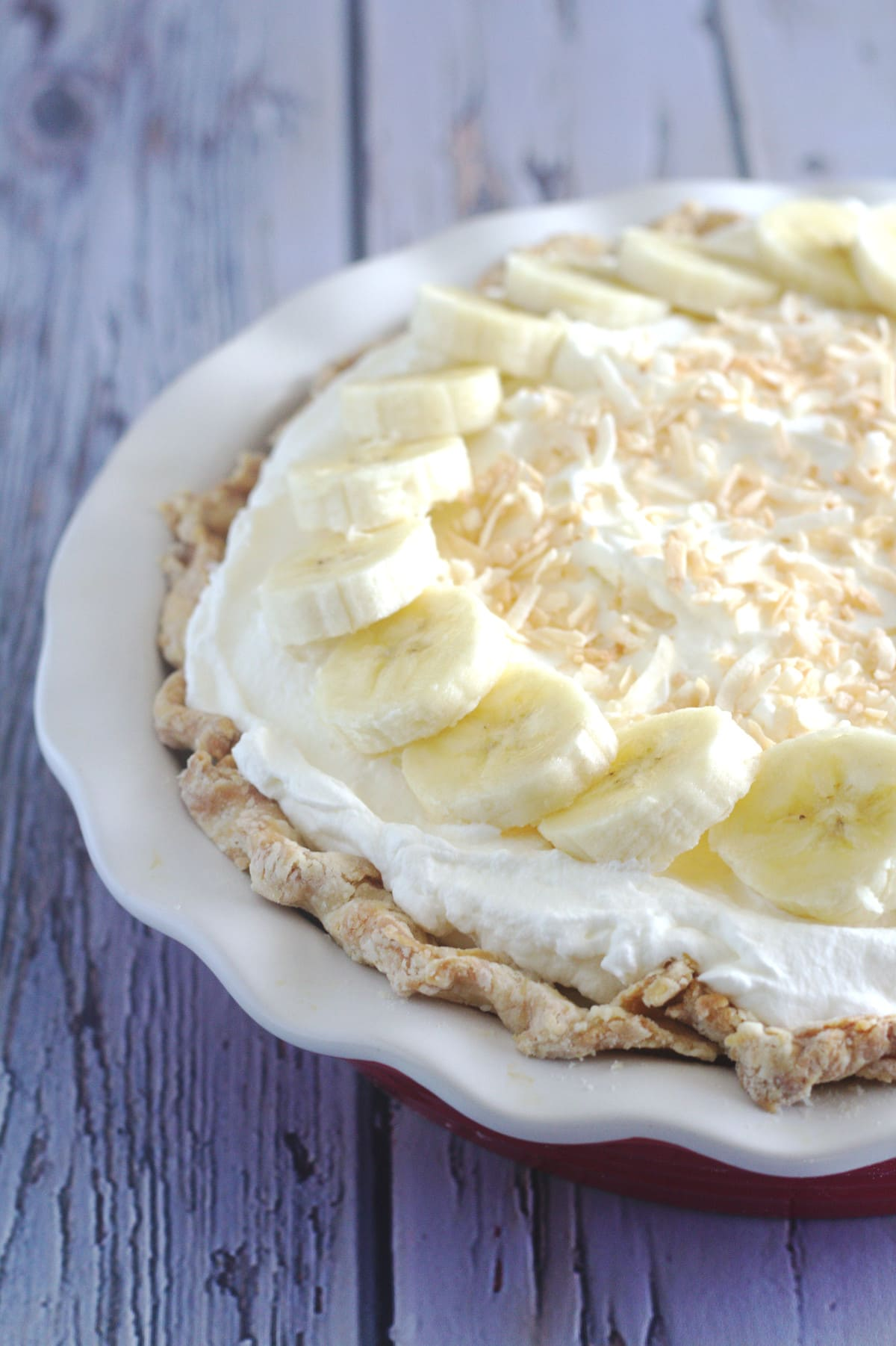 A full pie decorated with whipped crea, banana slices and toasted coconut flakes.