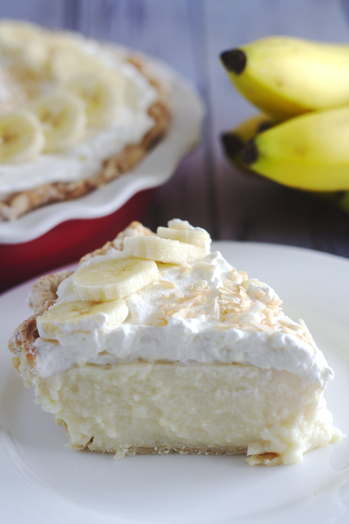 A slice of pie on a plate.  Bananas and the rest of the pie are in the background.