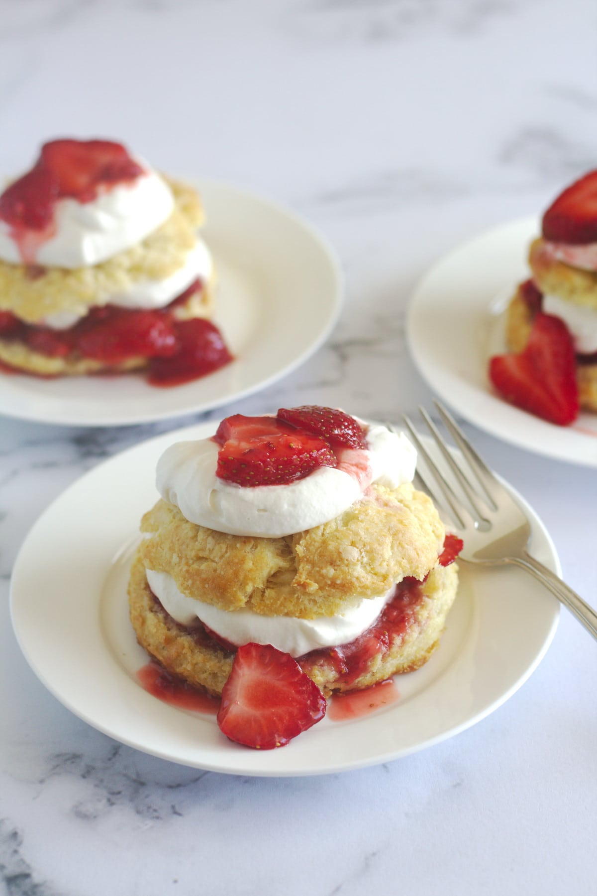 A strawberry shortcake on a plate with a fork.  Other plated strawberry shortcakes are in the background.
