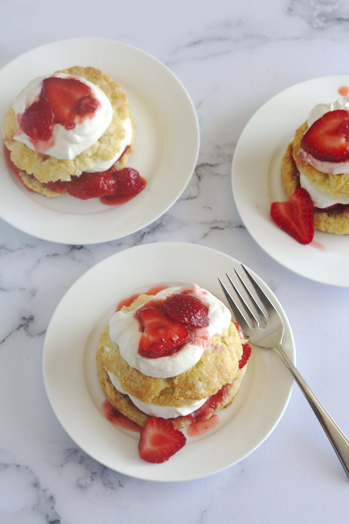 An above view of strawberry shortcakes on plates.  The bottom one has a fork on the plate.