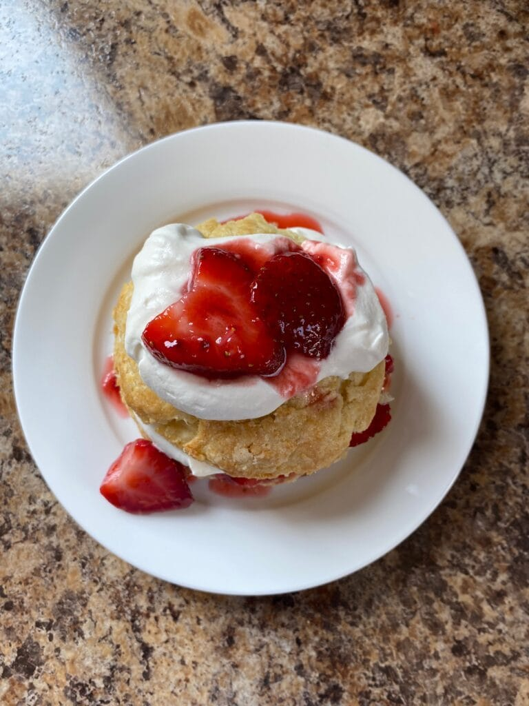 A biscuit with it's top half on and more sweetened whipped cream and strawberries on top.