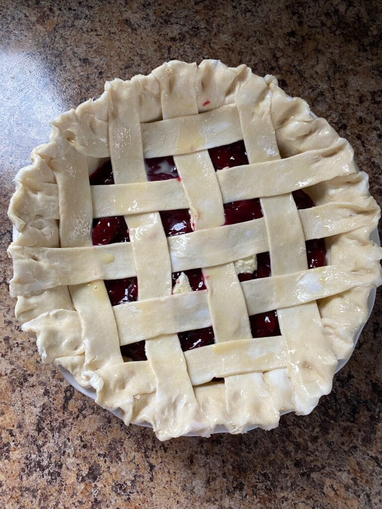 Lattice topping weaved on the pie.  Egg wash has been brushed on top and sugar scattered.