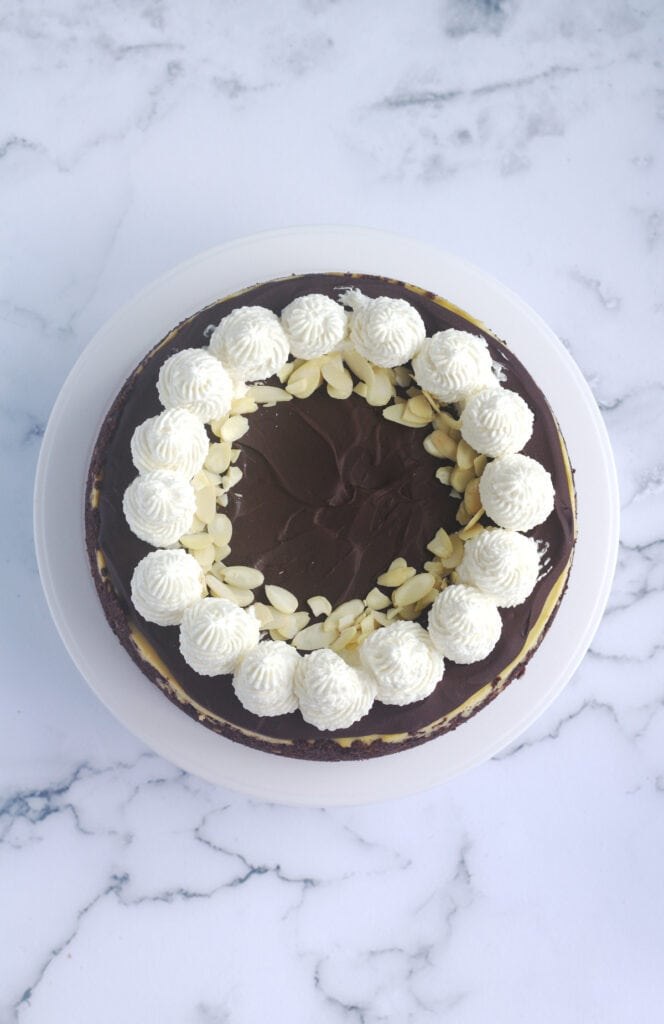 Cheesecake decorated with sweetened whipped cream and slivered almonds.