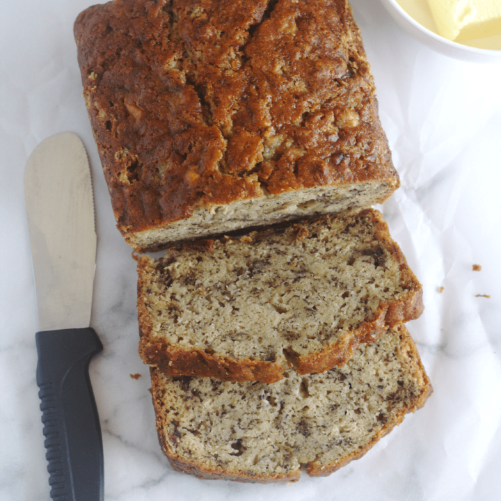 Banana bread with some slices cut from it. A spreading knife lays on one side of the bread and a bowl of butter on the other side.