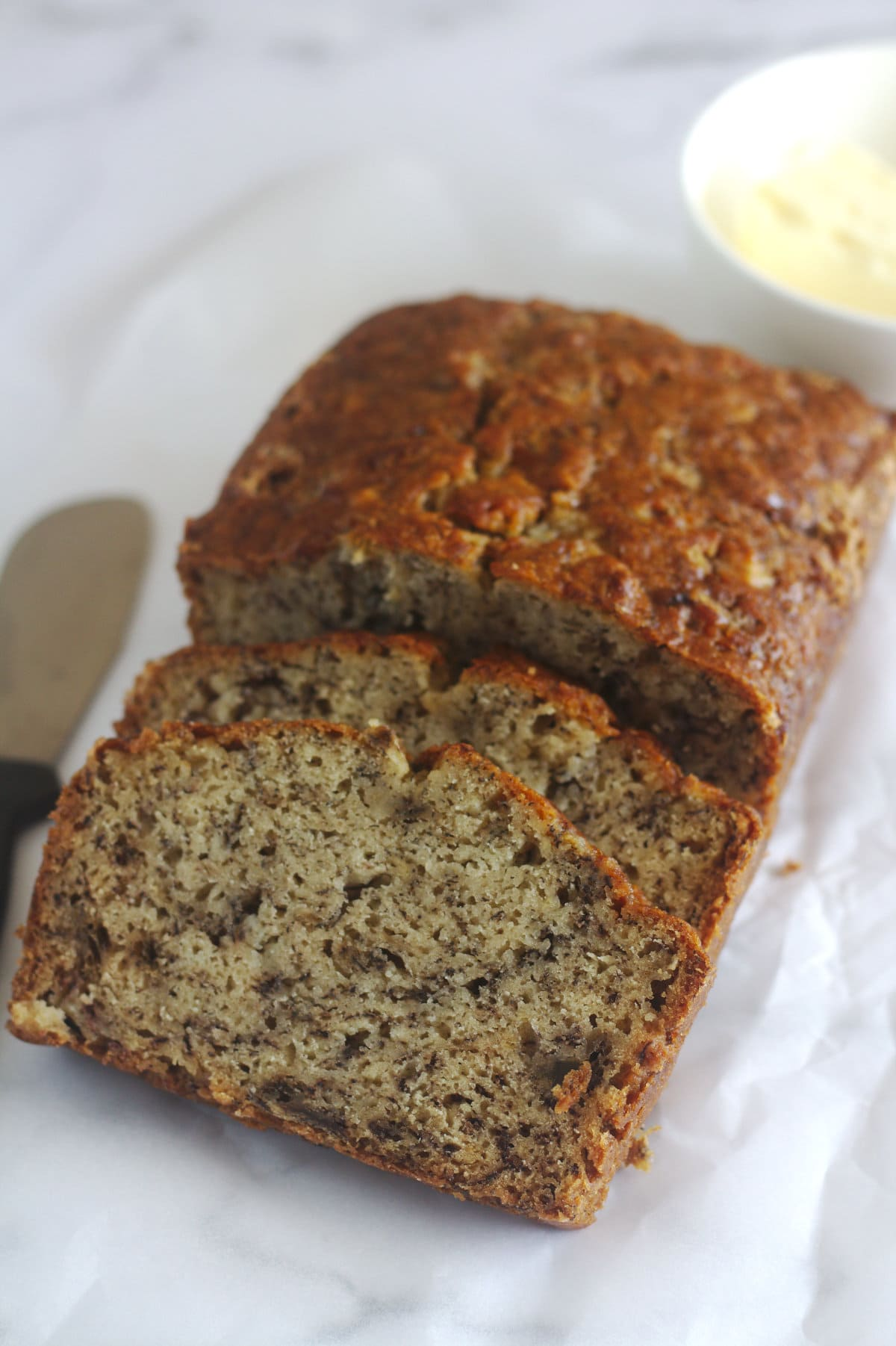 Banana bread with some slices cut from it.  A bowl with butter sits beside it, and a spreading knife on is on the other side.