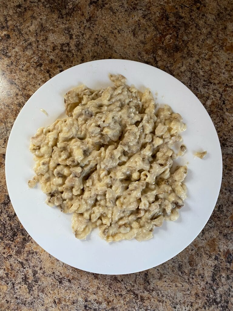 Bananas mashed up on a white plate.