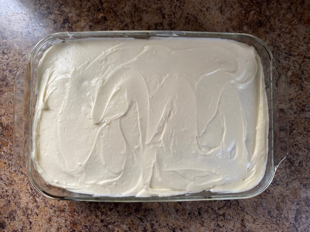 Cream cheese frosting spread over the cake in a baking dish.
