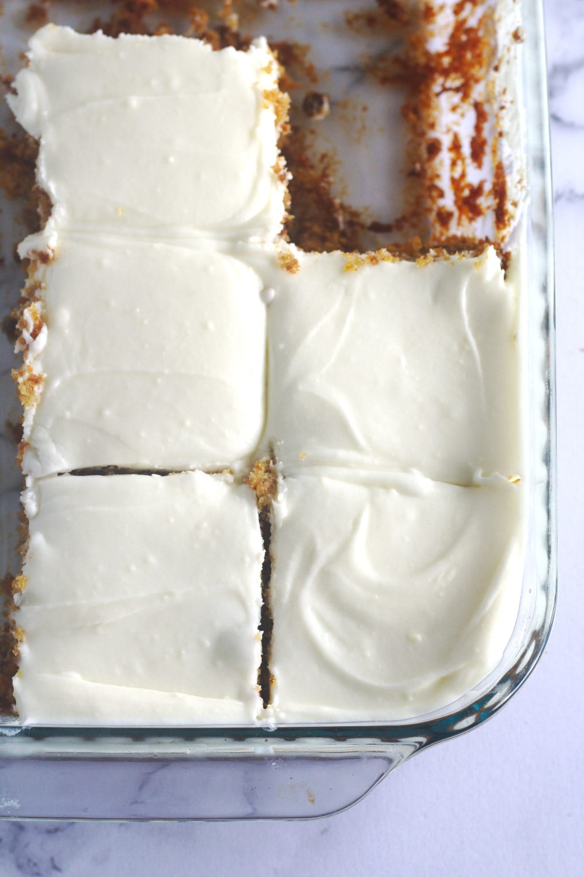Cake cut into slices in a baking dish.