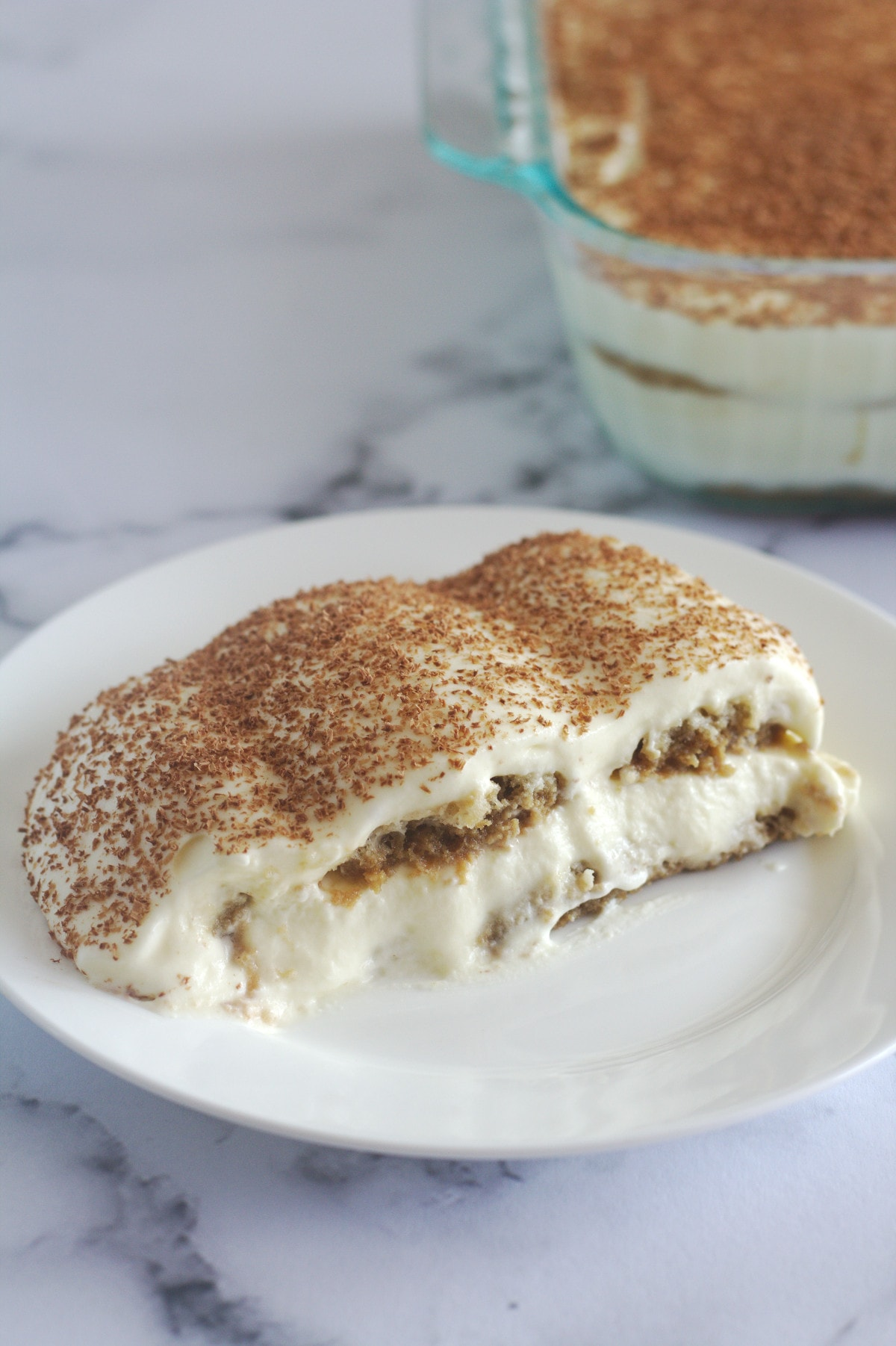 Tiramisu on a white plate with the rest of the cake in the background.