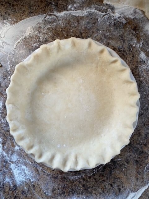 Pie dough in a pie plate.
