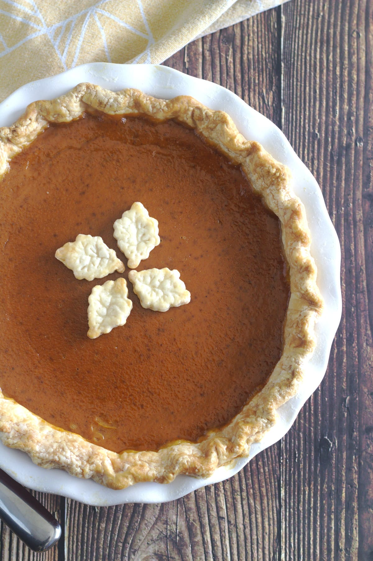 A pumpkin pie with leaf decorations on it.