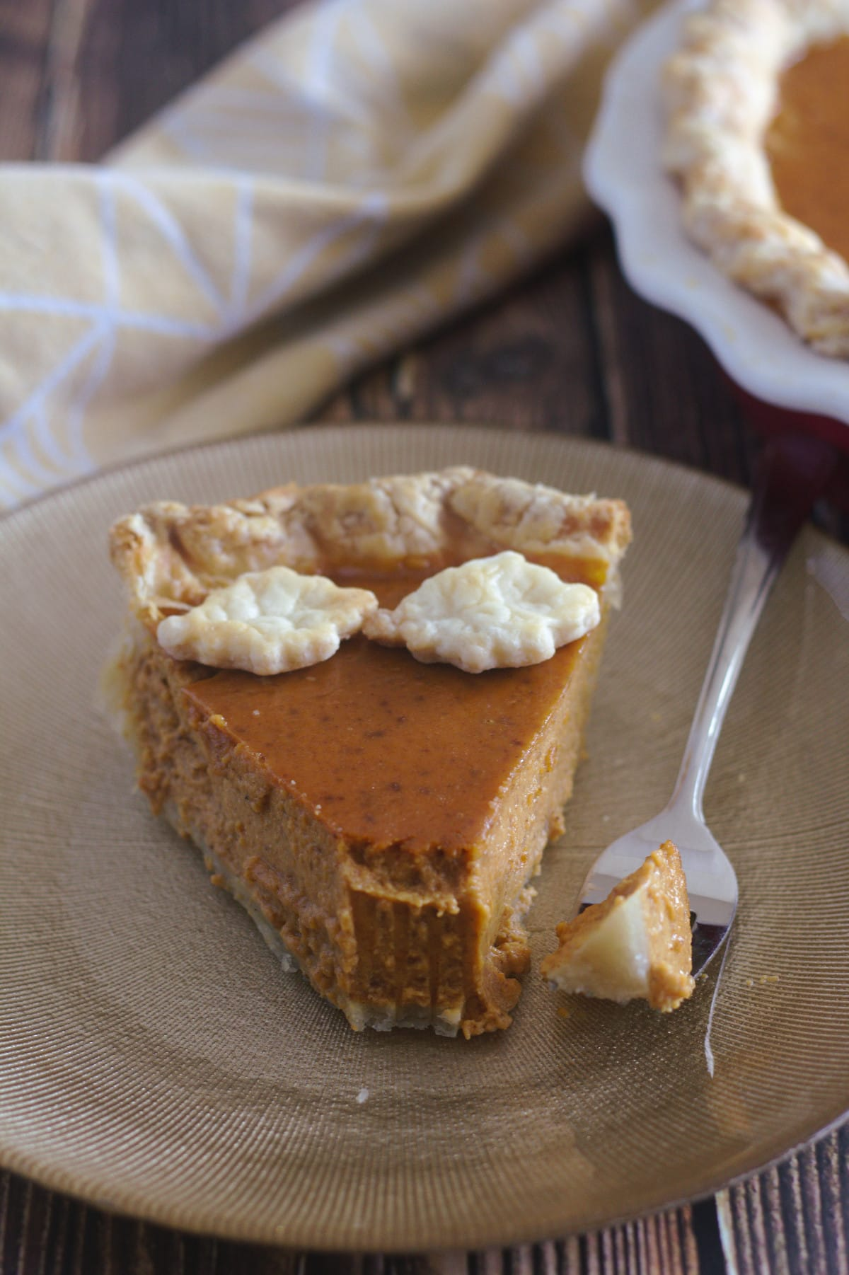 A slice of pie with a fork beside it.  The slice of pie is missing a chunk and it is on the fork.