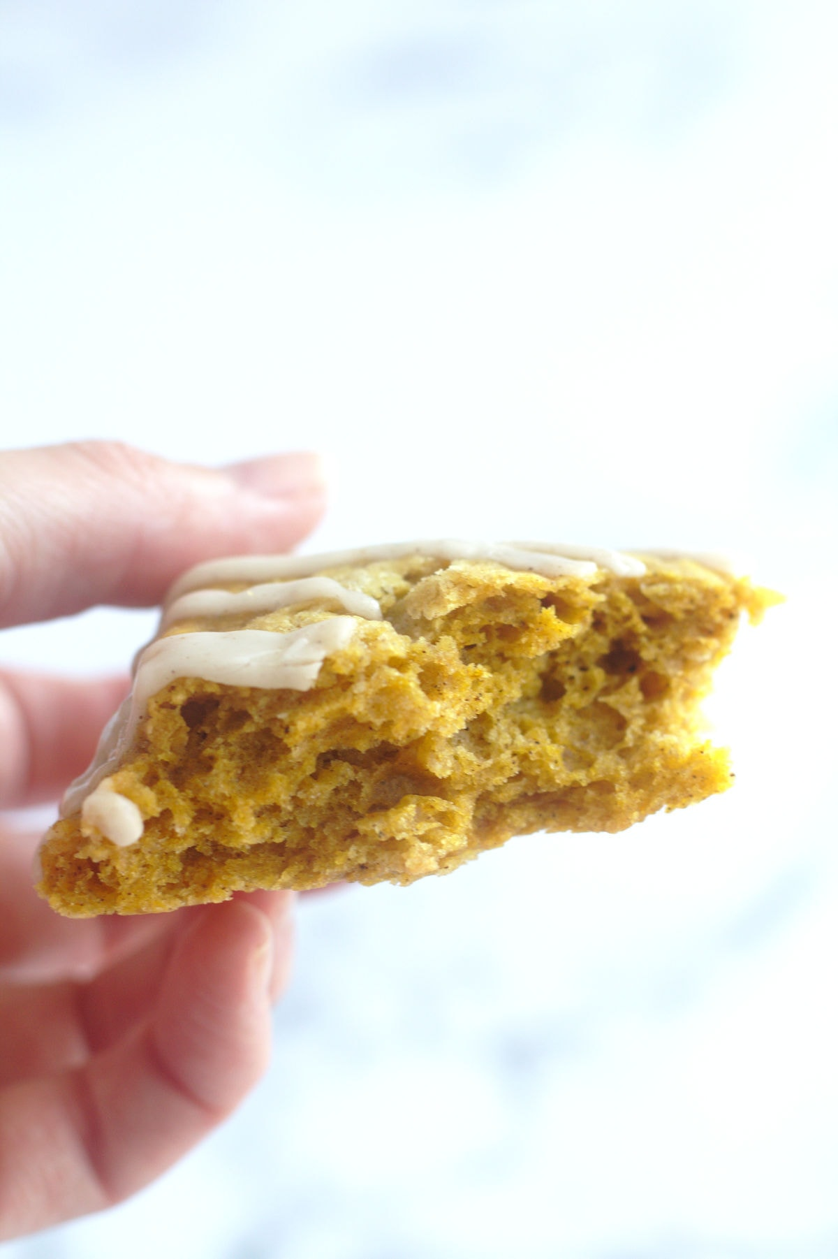A piece of scone with a bite out of it, being held in someone's hand.